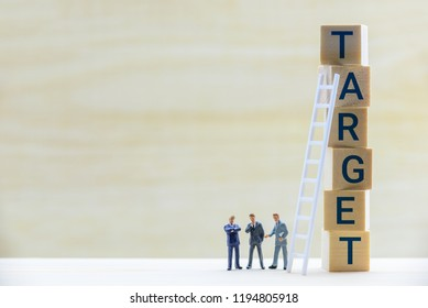 Business target market and company sales performance target concept : Miniature figurine top executive management team e.g CEO, CFO, CMO discuss / have a dialog on a firm / corporate financial target.
