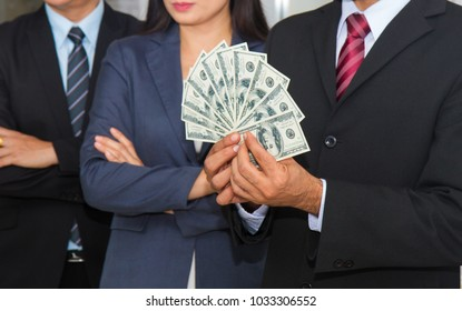 A Business team achievement and get the dollars banknotes from boss during the meeting.