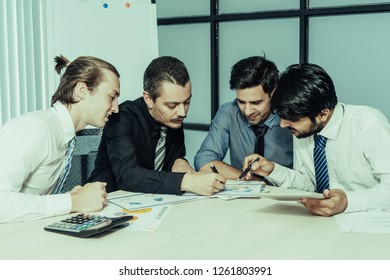 Business team analyzing financial report. Group of entrepreneurs concentrated on examining documents. Paperwork concept