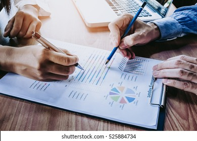 Business team analyzing income charts and graphs with modern laptop computer. Top view close up business analysis and strategy concept.