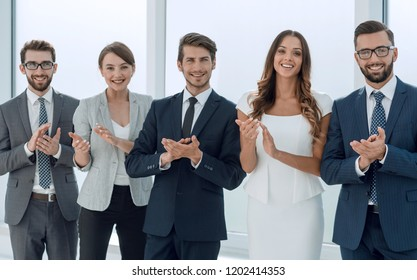 business team applauding while standing in the office