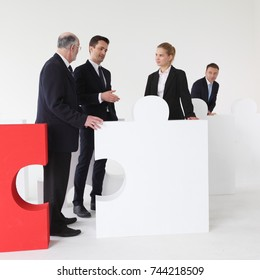 Business team assembling big puzzle on white background