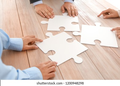 Business team assembling puzzle on wooden table