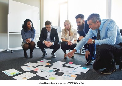 Business team brainstorming in office, crouching to look at assorted ideas on floor
