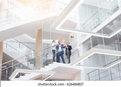 現代の明るいオフィスのインテリアで、ビジネスチームやビジネスマンが集まっています。若くてスタイリッシュなビジネスマンとノートパソコンを持つ女性が、職場で休憩時間に話す