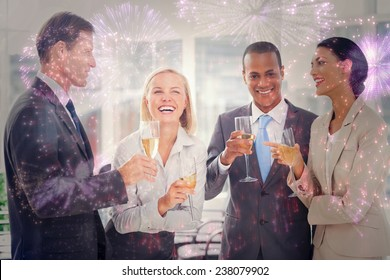Business team celebrating with champagne against colourful fireworks exploding on black background