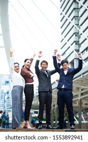 Business team celebrating and success concept. Four Asian business team success triumph with arms up