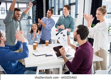 business team celebrating success together on workplace in office, young professional group concept