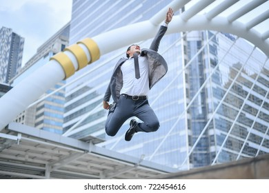 Business Team Celebration Party Success.Young successful businessman in suit rejoicing, jumping over cityscapes building background.Business People Success Achievement City Concept