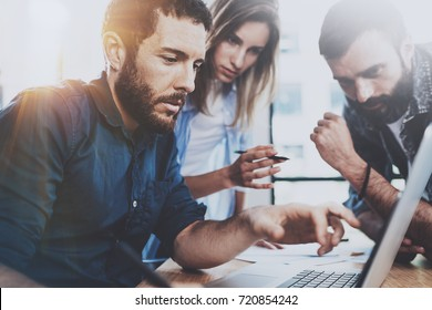 Business team concept.Young professionals discussing new business project in modern office.Group of three people analyze reports on laptop computer.Horizontal,blurred background.Flares