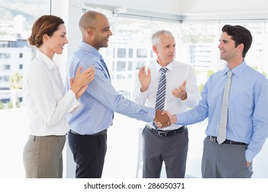 Business team congratulating their colleague in the office