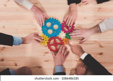 Business team connect pieces of gears. Teamwork, partnership and integration concept