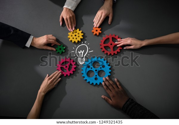 Business team connect pieces of gears to build a new creative idea. Teamwork, partnership and integration concept