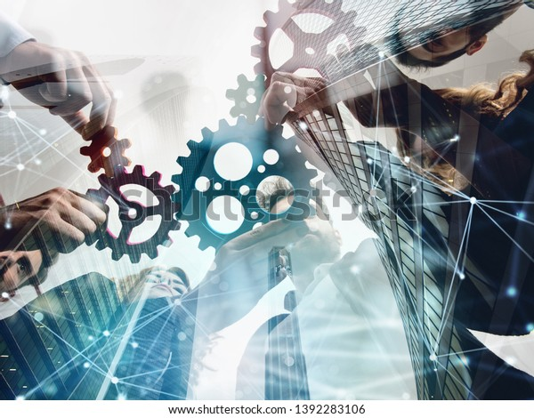 Business team connect pieces of gears. Teamwork, partnership and integration concept. double exposure with network effects