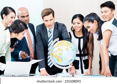 Business team discussing available market intelligence for outsourcing plans looking at globe, Indian, Caucasian, Chinese and Indonesian people