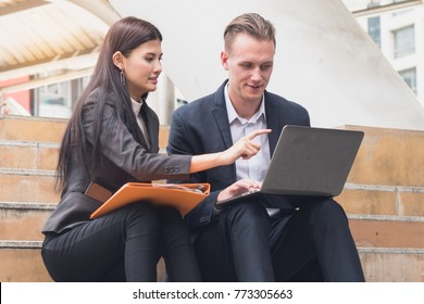 Business team discussing marketing plan in laptop computer. business woman pointing to computer screen explaining information to project teammates sitting work outdoors.