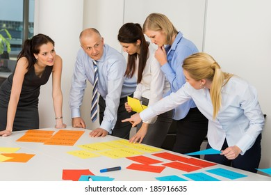 Business team discussing multicolored labels in boardroom meeting