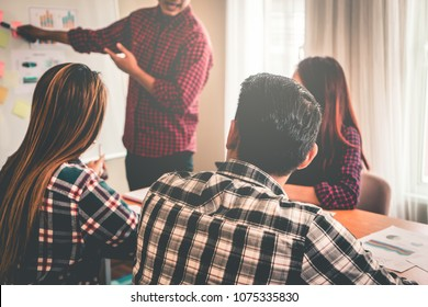Business team is discussing on white board in meeting
