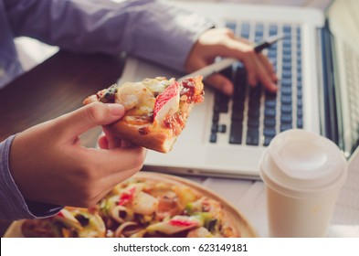 Business team is eating pizza at work while working