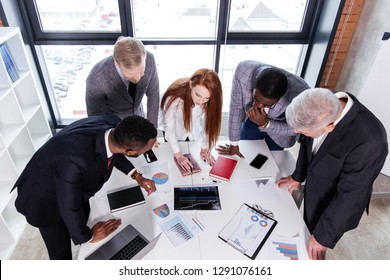 Business team of ethnic people bent down in front of the table looking at the financial sales schedule and talking to each other. Young red-haired employee stands in the middle between adult men