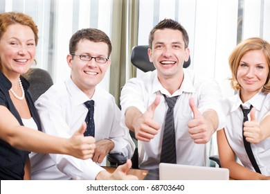 Business team expressing positivity with thumb-ups during meeting in board room in Hi Res. Two men and one woman smiling for camera and showing their teeth from happiness.