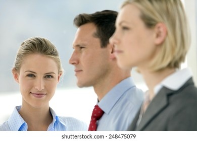 Business team - Focus on businesswoman looking at camera - other executives looking away