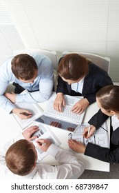 A business team of four sitting at one table and working