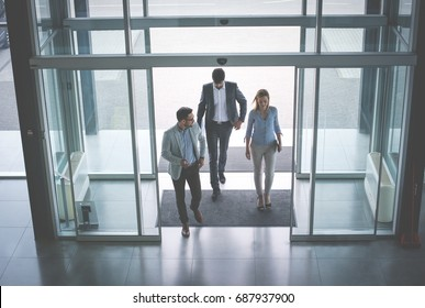 Business team gets to work. Three people entering the building.