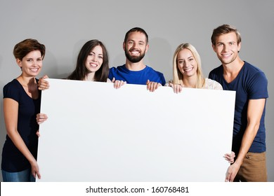 Business team or group of diverse young professional friends holding a blank white sign in front of them with friendly smiles for your text or advertisement