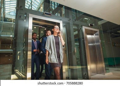 Business team group exit on elevator. Business people in a large glass elevator in a modern office