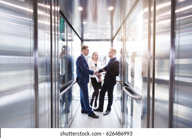 Business team group going on elevator. Business people in a large glass elevator in a modern office