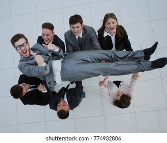 Business team happily throws up their colleague in the air celeb