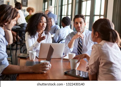 Business Team Having Informal Meeting Around Table In Coffee Shop