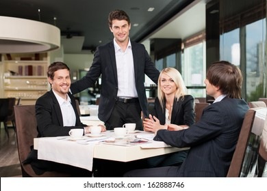 Business team having meeting at the restaurant. One man standing