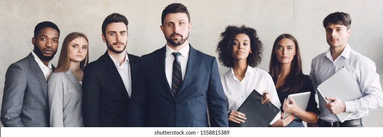 Business team headed with boss, posing to camera over grey wall in office