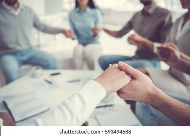 Business team is holding hands together while sitting in circle in office