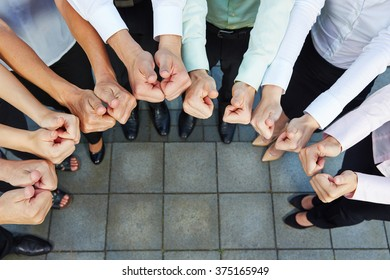 Business team holding many thumbs up in a semicircle from above
