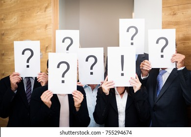 business team holding pieces of paper with question marks and one exclamation mark. concept shot used to depict cluelessness or confusion of the team, with one memeber saving the day.