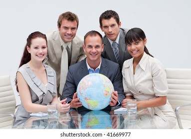 Business team holding a terrestrial globe in the office. Global business concept