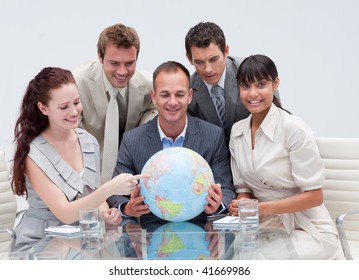 Business team holding a terrestrial globe in the office. Worldwide business concept