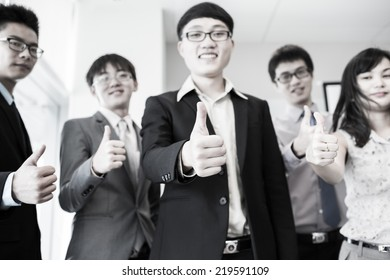 Business team holding their thumbs up.Asian