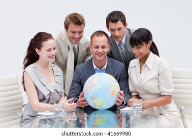 Business team holding the world in the office. Global expansion