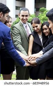 business team joyful hands together outdoors