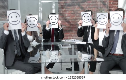 business team keeps smiley icons sitting at the Desk