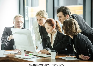 Business team look at one computer monitor having discussion in office