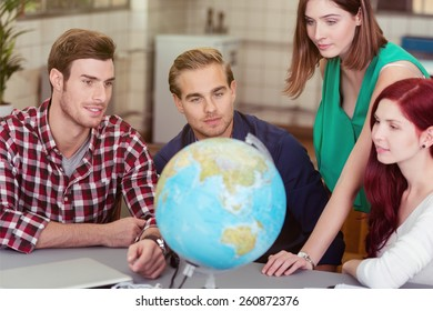Business team looking for global markets as they plan the expansion of their business sitting around a table in the office with a globe