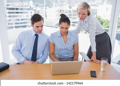 Business team looking at laptop on desk in office