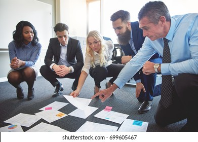 Business team looking at papers on floor with manager pointing to one idea