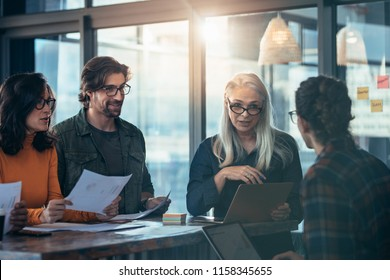 Business team of meeting around a table in office. Group of business man and woman discussing work in office.