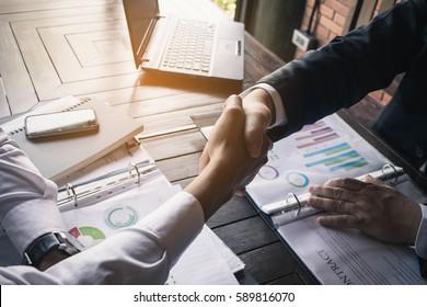 Business Team Meeting Handshake Applaud Concept. Business partners handshaking over business objects on workplace.